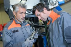 Airplanes mechanic and co-worker checking metal object royalty free stock photo