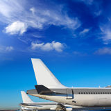 Airplanes in a row under blue sky Stock Images