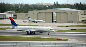 Airplanes on runway. General view of airport, hangars and taxiing aircraft royalty free stock image