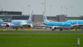Airplanes at Shiphol Airport apron. AMSTERDAM, THE NETHERLANDS - JULY 25, 2017: Airplanes of Royal Dutch Airlines KLM and TUI Fly taxiing on apron, Shiphol stock footage