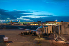 Airplanes at Singapore Changi Airport International terminal wit. Airplanes at the terminal in Singapore Changi airport at the dusk. Singapore 2016 Royalty Free Stock Photo