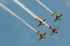 Airplanes in the sky. A team of four airplanes in red, yellow and blue flying together high up in the sky on an air show, concept of teamwork Stock Photography