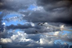 Airplanes with smoke trails performing acrobatic maneuvers royalty free stock photography