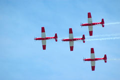 Airplanes teamwork. Four airplanes in red and white flying in the air at the flight show Stock Image