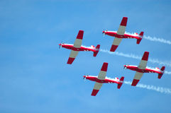 Airplanes teamwork. For small propeller airplanes in red and white on a flight show flying in the air Stock Photos