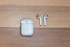 Airpods sem fio brancos no fundo de madeira com caixa do carregador, foco escolhido foto de stock