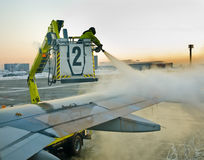 Airport. Man defrosting plane's wing before departure early in the morning stock images
