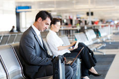 At airport. Businessman and businesswoman using laptop and tablet computer at airport stock photography