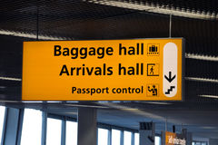At the airport. Signpost pointing towards baggage and arrivals hall and passport control at Amsterdam Schiphol airport Stock Photo