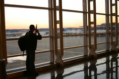 The airport. Traveller with backpack talking on cellphone at dawn at airport royalty free stock images