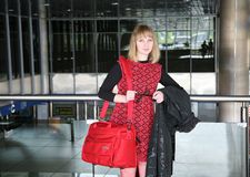 At the airport. Blonde with a red road bag at the airport Royalty Free Stock Photos