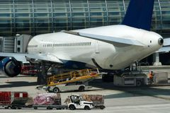 Airport, airplane, loading cargo. Airplane is parked on airport and cargo loading is in progress Stock Images
