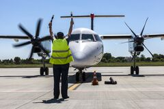 Free Airport мarshal In Front Of A Propeller Plane At The Airport. Royalty Free Stock Photos - 186867078