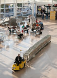 Airport Baggage Cart Hauler. An airport employee hauls a train of baggage carts across the main floor Stock Images