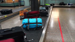 Airport Baggage Claim Luggage Conveyor. Bags go around until the traveler picks them up at the airport stock video footage