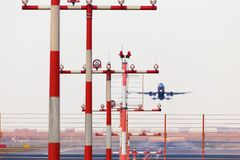 Airport beacons with starting airplane in the daylight. Some airport beacons with starting airplane in the daylight Stock Images