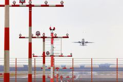 Airport beacons with starting airplane in the daylight. Some airport beacons with starting airplane in the daylight Royalty Free Stock Photography