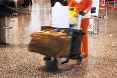 Airport blur. At the airport - tourist or worker running to the gate with trolley and baggage Royalty Free Stock Photography