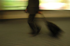 Airport Blurs 2. Solitary male traveler with rolling baggage. He is also holding a mobil phone Royalty Free Stock Images