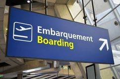 Airport boarding sign from a low angle view. Boarding sign at Charles de Gaule International Aiport in Paris, France, written in French and in English, from a royalty free stock photos