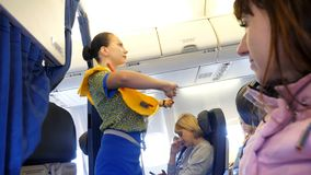 AIRPORT BORISPOL, AIRLINES UIA - NOVEMBER 20, 2017: in the cabin of the aircraft, the stewardess conducts briefing. Before take-off, shows how to dress and stock video