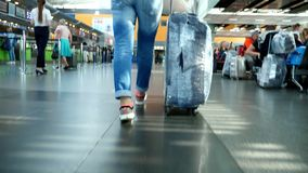 AIRPORT BORYSPIL, UKRAINE - OCTOBER 24, 2018: close-up. back view. female legs in sneakers. Woman, Traveler, passenger. With her wrapped suitcase, luggage stock video footage