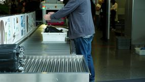 Airport Boryspil, Ukraine - October 24, 2018: Male passenger puts belongings in plastic tray, box on a conveyor belt, in. Front of the x-ray scanner for stock video footage