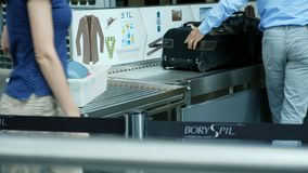 Airport Boryspil, Ukraine - October 24, 2018: passengers put their belongings in plastic trays, boxes on a conveyor belt. In front of the x-ray scanner for stock video footage