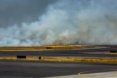 Airport Brush Fire Closes San Salvadore Airport. SAN SALVADORE, EL SALVADOR - MARCH 3, 2013: Brush fire flames and smoke close San Salvador International Airport Stock Image