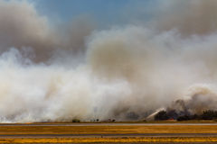 Airport Brush Fire in El Salvadore, Central America. SAN SALVADORE, EL SALVADOR - MARCH 3, 2013: Firemen wet down brush as fire closes in on end of runway at San Stock Photo