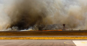Airport Brush Fire in El Salvadore, Central America. SAN SALVADORE, EL SALVADOR - MARCH 3, 2013: Brush fire threatens runway and radar station closing San Stock Photos