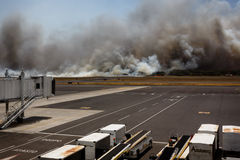 Airport Brush Fire in El Salvadore, Central America from terminal. SAN SALVADORE, EL SALVADOR - MARCH 3, 2013: Brush fire closes San Salvador International Royalty Free Stock Image