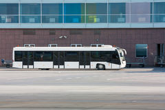 Airport bus and baggage carts near the terminal Stock Images