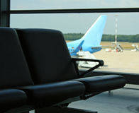 Airport chair. Airport couch chair with airplane in background Royalty Free Stock Photo