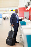 Airport check in. African businessman standing by airport check in counter Stock Image