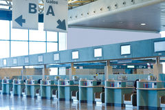 Airport check-in desks. Airport check-in area scene with check in desks and gates signs Royalty Free Stock Photo
