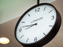 An airport clock showing London time zone Stock Image