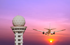 Airport control tower and commercial airplane landing at sunset Stock Photos