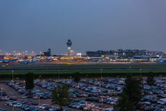 Airport control tower at Schiphol airport the Netherlands. Airport control tower, airplanes and a car park in the evening on Schiphol airport in the Netherlands royalty free stock photography