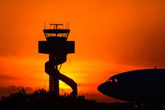 Airport control tower at sunrise, with jet silhouette Stock Image
