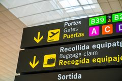 Airport departure and baggage claim signs. In english and Spanish located in Barcelona, Spain Stock Image