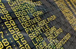 Airport Departure Board with USA destinations. Close-up of an airport departure board to usa cities destinations, with environment reflection.Part of a series stock photography