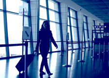 Airport departure gate. Casual woman with a roller luggage walking in the airport departure gate royalty free stock image