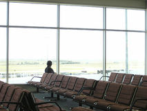 Airport departure lounge chairs. A lone man waits in an empty airport departure lounge Stock Images