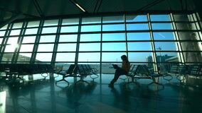 Airport departure lounge and a woman with a laptop sitting in it. 4K stock footage
