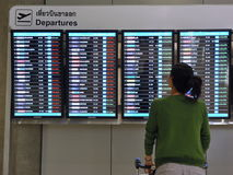 Airport Departures Board. A traveller views a departures board at Suvarnabhumi International Airport on July 6, 2012 in Bangkok, Thailand. The airport handles 45 Stock Photos