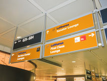 Airport direction signs. Signs indicating directions to gates and various Lufthansa lounges on a German airport stock images