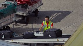 Airport employee controls luggage. DUSSELDORF, GERMANY - JULY 21, 2017: Young male airport employee with modern haircut is staying near luggage conveyor and stock footage
