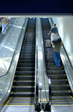 Airport escalator. (12MP camera). Focus is on the right upper man with luggage Royalty Free Stock Photos
