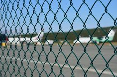 Airport fence closeup photo with blurred aircrafts Royalty Free Stock Photography